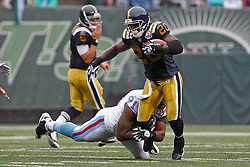 Sept 27, 2009; East Rutherford, NJ, USA; New York Jets running back Thomas Jones (20) eludes the tackle of Tennessee Titans defensive end Jason Jones (91) during the first half at Giants Stadium.