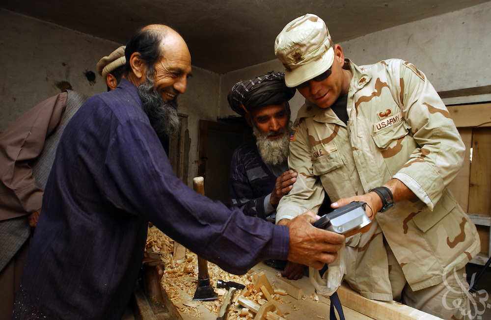 U.S. Army Maj. Bryan Cole, from the 489th Civil Affairs Batallion based in Knoxville, TN, shows Afghan carpenters the digital photo he shot of them May, 26, 2002 at the Parwan Institute for Teachers Training in Charikar, Afghanistan. The 489th Civil Affairs division delivered a load of blankets to the institute for students returning to the dorms and classes next week.