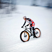 SHOT 2/9/13 5:08:10 PM - Jake Wells of Avon, Co. descends downhill during the On-Snow Mountain Bike Crit event at the second annual Winter Mountain Games presented by Eddie Bauer at Vail Ski Resort in Vail, Co. Wells won the Fat Tire Male class. The Winter Mountain Games feature competitions in X-Country On-Snow Mountain Bike Races, mixed climbing, Telemark Big Air,Best Trick Bike and On-Snow Mountain Bike Crit with more than$60,000 in prize money on the line. (Photo by Marc Piscotty / © 2013)