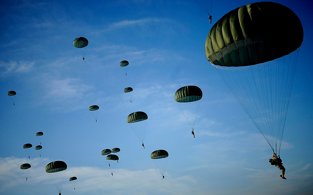 U.S. Army Soldiers with the 82nd Airborne Division descend under a parachute canopy to earn foreign jump wings during the 11th Annual Randy Oler Memorial Operation Toy Drop at Fort Bragg, North Carolina, Dec. 6, 2008. Over 1200 Soldiers donated a toy for a lottery ticket to win a chance to jump under a German or Irish Jumpmaster to earn their foreign jump wings. — © /