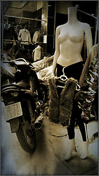 Fur vest hangs from the pants of a bare-chested mannequin outside a shop in Hanoi, Vietnam, Southeast Asia