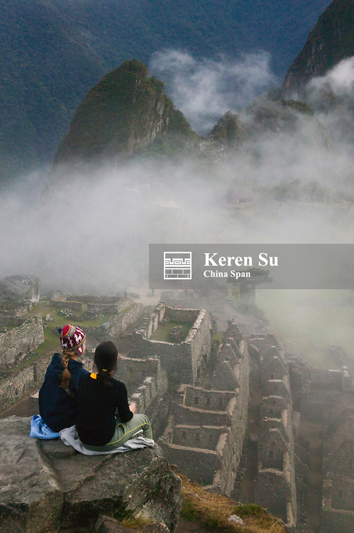 Tourists at ancient ruins of Machu Picchu in the Andes Mountain in early morning mist, Peru