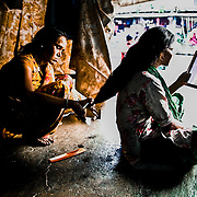 SM is a former prostitute. Her husband is an alchoolic and beats her up everynight. She doesn't have anywhere else to go. She is extremely poor and try to make out a living working as a beautician for other prostitutes in the Red District area in Mumbai
