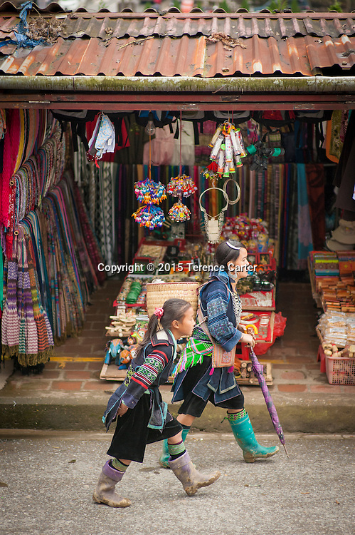 Hilltribe women walk through the markets in Sapa, Vietnam.