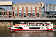 Tourists boat cruise on the river Ouse passing The York Herald building formerly a press hall now housing a cinema and bars.