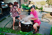 Kathy Spataro and daughter Amy and Becky get quite wet while teaming up to wash a chicken being ready for fair competition.
