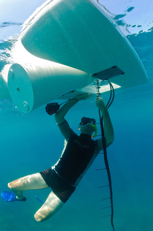 Sven Fautz of Bali Diving Academy checking the mooring of a Resen Wave generator used to power a Biorock installation, Pemuteran, Bali, Indonesia.
