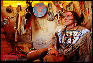 Plains Indian reenactor Michael Terry, a Seminole himself, sits in his buffalo-hide teepee amid wealth of Indian artifacts; Fort Union, North Dakota