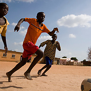 Children play football at the Tangory Transgambienne 2 primary school in the town of Bignona, Senegal on Wednesday June 13, 2007.
