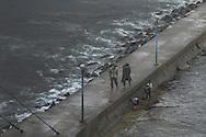 Boys shellfishing near a jetty while two men look on, Wonsan, North Korea.