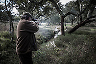 Ant&oacute;nio Manuel Barata shooting a deer. <br /> <br /> &quot;The Pose and the Prey&quot;<br /> <br /> Hunting in my imagination was always more like taxidermy &mdash; as if the prey was just a mere accessory of the hunter's pose for his heroic photograph &mdash; the real trophy.<br /> <br /> When I decided to document the daily lives of Portuguese hunters, I had in my memory the &quot;clich&eacute;&quot; from the photographer Jos&eacute; Augusto da Cunha Moraes, captured during a hippopotamus hunt in the River Zaire, Angola, and published in 1882 in the album Africa Occidental. The white hunter posed at the center of the photograph, with his rifle, surrounded by the local tribe.<br /> <br /> It was with this clich&eacute; in mind that I went to Alentejo, south of Portugal, in search of the contemporary hunters. For several months I saw deer, wild boar, foxes. I photographed popular hunting and private hunting estates, wealthy and middle class hunters, meat hunters and trophy hunters. I photographed those who live from hunting and those who see it as a hobby for a few weekends during the year. I followed the different times and moments of a hunt, in between the prey and the pose, wine and blood, the crack of gunfire and the murmur of the fields .<br /> <br /> I was lucky, I heard lots of hunting stories. I found an essentially old male population, where young people are a minority. Hunters, a threatened species by aging and loss of economic power caused by the crisis in the South of Europe.<br /> <br /> The result of this project is this series of contemporary images, distant from the &quot;cliche&quot; of 1882.<br /> <br /> &mdash; Antonio Pedrosa