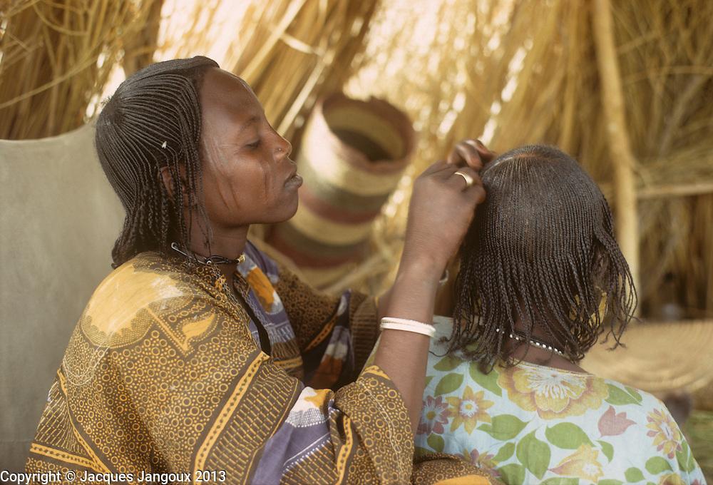 Africa, Sahel region, Chad, Islands of Lake Chad. Woman grooming another woman´s hair. The Kanembu speak a Nilo-Saharan language.
