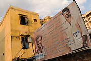 Advertising billboard in the flats of Santhome. Santhome Beach and adjoining Marina Beach in Chennai, India were hit hard by the 2004 Tsunami. Fishermen and their families were the main victims living in their lightweight huts on the long and flat beaches of the area. All structures within 300 metres of the sea have now been banned and any left standing after the Tsunami were demolished. The fishermen and their families have now been relocated to government blocks of flats which has become a Santhome slum for fishermen and their families.
