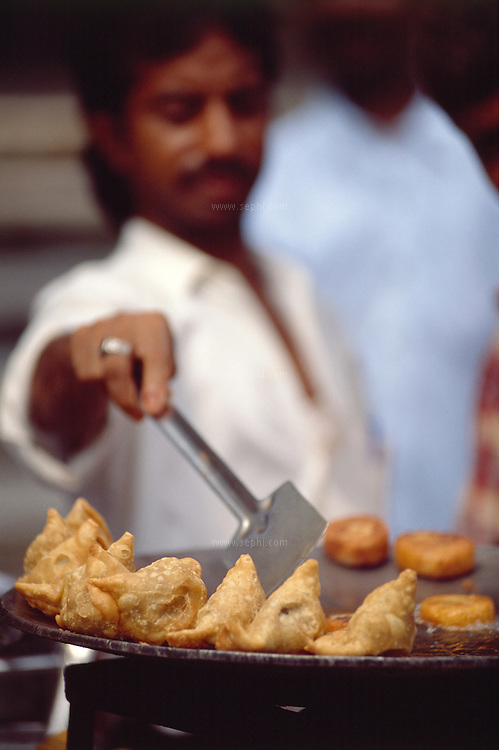 Samosas on the Tawa and the vendor attending the Aloo Tikkis in the hot oil. Mumbai, March 2006