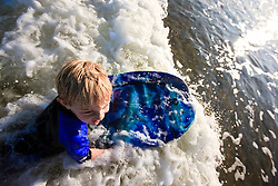 A boy (age 6) boogie boarding at Popham Beach State Park in Phippsburg, Maine.