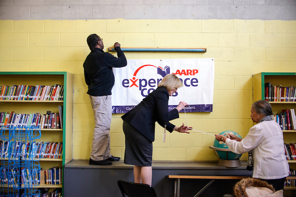 Philadelphia, Pennsylvania - October 24, 2013:<br /> <br /> AARP Experience Corps volunteer Michael Stewarts, left, AARP Experience Corps Branch Director Catherine Mesaros, middle, and Cramp Elementary School Experience Corps School Liaison Helen Johnson, right, hang the organization's sign in Cramp Elementary School's library, readying it for interviews.