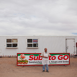 Philip Skinner poses for a portrait outside his sandwich shop in Columbus, New Mexico. Recently federal authorities arrested the mayor, police chief, and trustees who were allegedly operating an illegal gun running ring.
