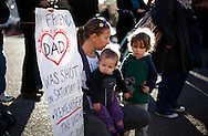 Susan Shobe (L) with her children Violet Schorr, 1,  (C) and Willow Schorr, 3, (R) kneels for a moment of silence at a memorial outside the hospital where victims of the shootings are recovering in Tucson, Arizona January 10, 2011.  Shobe's best friend's father Ron Barber was shot in the attack. Barber, district director for congresswoman Gabrielle Giffords spent more than six hours in surgery January 8 after being shot twice during the shootings that left six people dead.  REUTERS/Rick Wilking (UNITED STATES)