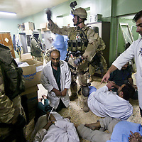 A soldier with US Special Forces, center, and a soldier with the Iraqi 36th Commando Battalion, left, part of the Iraqi Special Operations Force Brigade, attempt to identify doctors that were detained after US Special Forces and Iraqi troops stormed Falluja Hospital in Falluja, Iraq. November 2004.