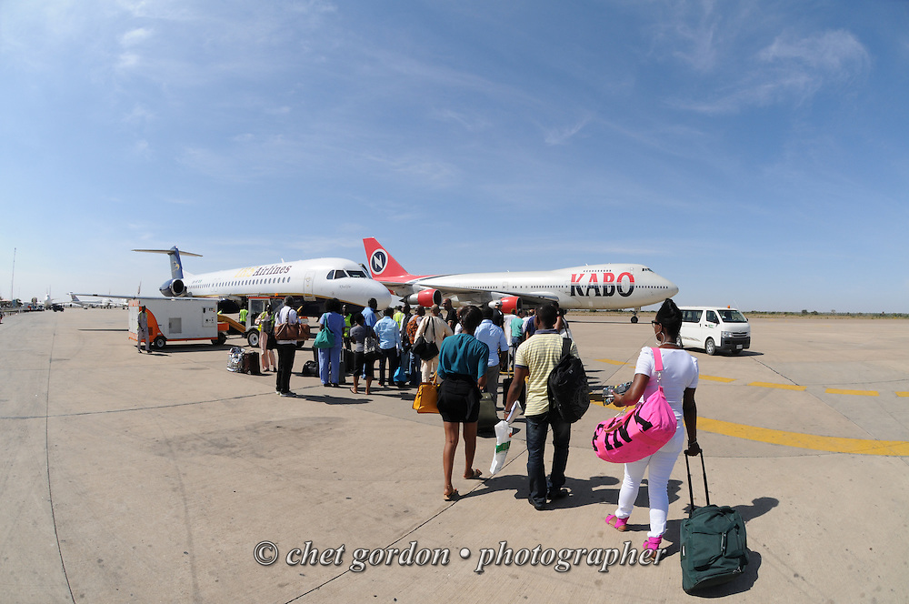 Passengers board their departing aircraft (left) at Mallam Aminu Kano International Airport in Kano, Nigeria on Friday, December 7, 2012.