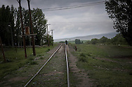 Akyaka resident on his way home from town walking along railway trucks.<br /> Akyaka is a last town and train stop on the way to Armenian border-and Gyumri  in Armenia .Border is about 10 km further on.