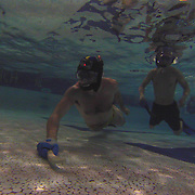 Andrei Savu, LEFT,  swims towards the goal post during a pick up game of underwater hockey Saturday, May 16, 2015, at Clarence Fraim Senior Center in Wilmington, Delaware.