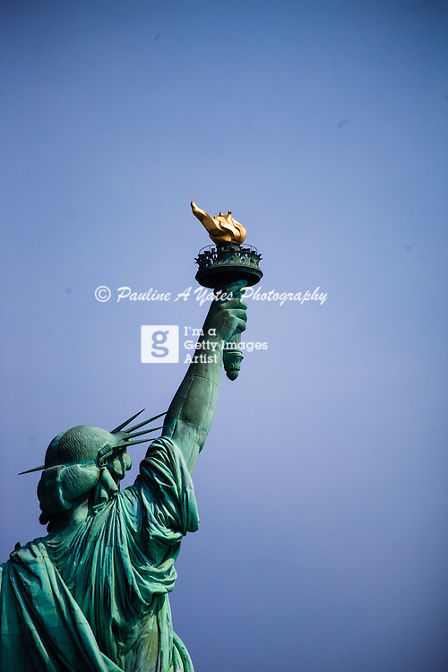 The statue of Liberty from the back. Lamp high in the clear blue summer sky.<br /> <br /> All posters are self-fulfilled. Prices vary depending on poster size and quality. Delivery is usually &pound;3.75.<br /> <br /> For poster orders please email: poster@paulineayates.com