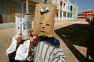 Crianças brincam nas ruas da Vila do Maio, ostentando máscaras de Carnaval improvisadas.