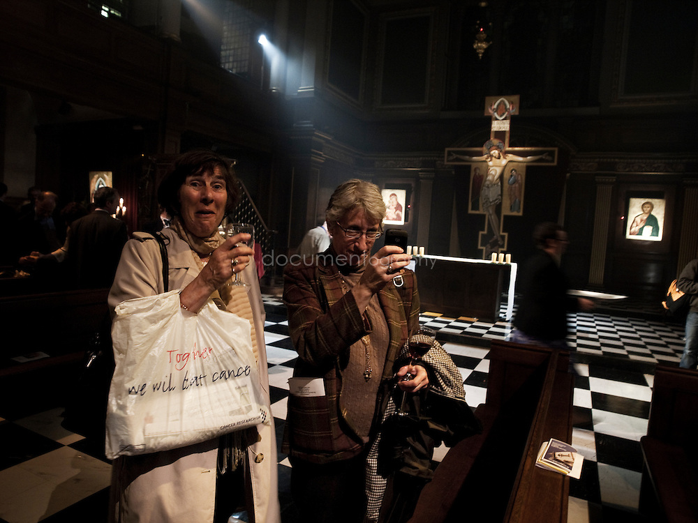 Two ladies photoghaph the archbishop after the blessing of an icon by, Rowan Williams at St andrews church in Holborn, london.