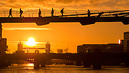 Early Morning sunrise over Millennium Bridge and Tower Bridge as people commute to work.