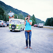 Girl taking a photo outside of the Brown Bear Saloon in Indian, Alaska. 2009
