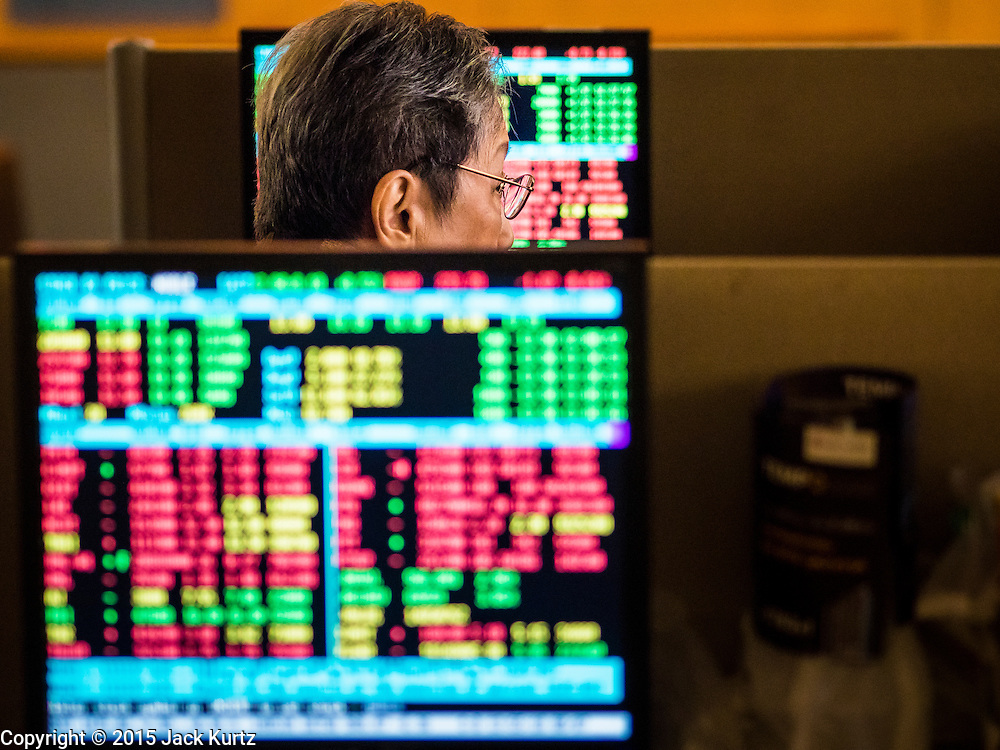 08 JULY 2015 - BANGKOK, THAILAND:  A person watches the prices of Thai stocks at a brokerage house in Bangkok. Thai financial markets and the Thai Baht both lost value Wednesday. The stock market, the Stock Exchange of  Thailand (SET) closed at 1,470.25, down 13.52 or 0.91%, from Tuesday. The Thai Baht closed at 33.90 Baht to 1 US Dollar, it's lowest point since September 2009. Economists blamed the drop in the Chinese stock markets and uncertainty over the EU's handling of the Greek budget crisis for the drops in Thai markets.   PHOTO BY JACK KURTZ