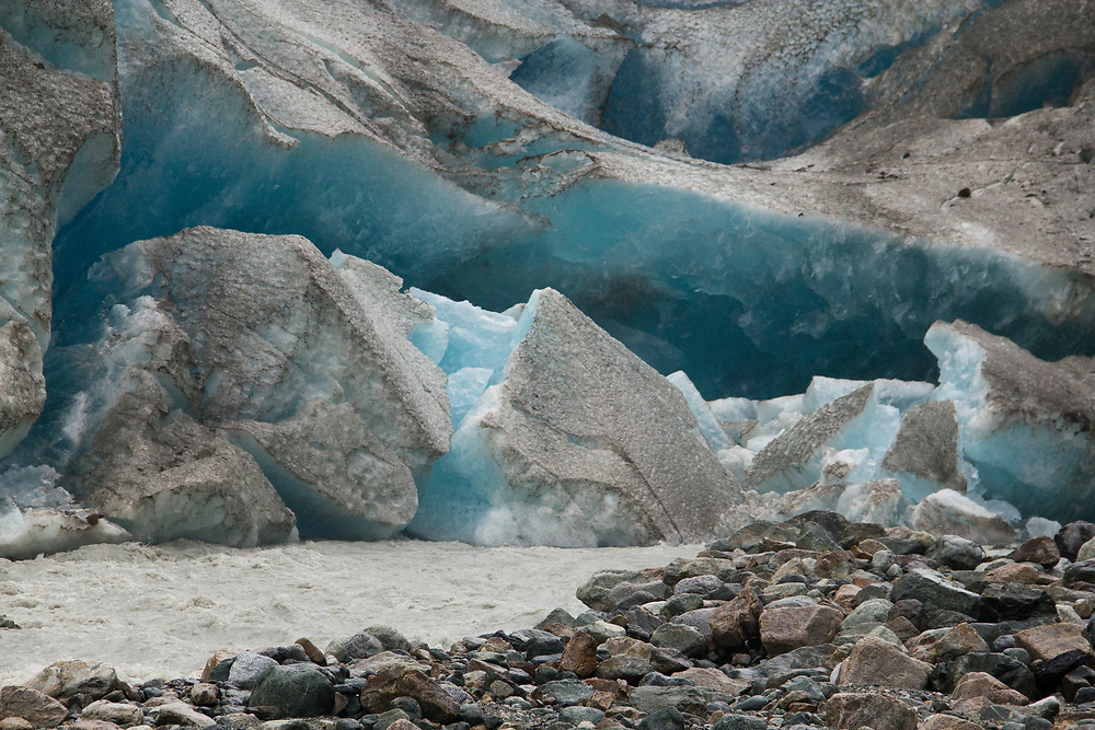 The terminus of the Reid Glacier sheds a large chunk of blue ice above its outwash stream.