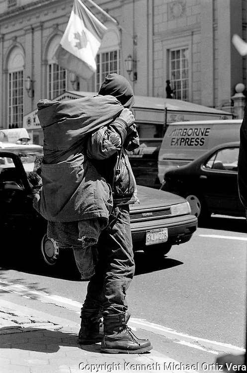 A homeless man waits on the corner of 60th Street and 5th Avenue to cross the street.