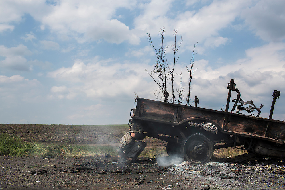 OKTYABRSKAYA, UKRAINE - MAY 14: A man salvages scrap metal from a destroyed truck on May 14, 2014 in Oktyabrskaya, Ukraine. Pro-Russian militants ambushed Ukrainian troops nearby the day before, killing seven and wounding another eight in the most deady attack yet on Ukrainian forces. (Photo by Brendan Hoffman/Getty Images) *** Local Caption ***