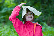 Young girl with butterbur leaf on her head, Scotland