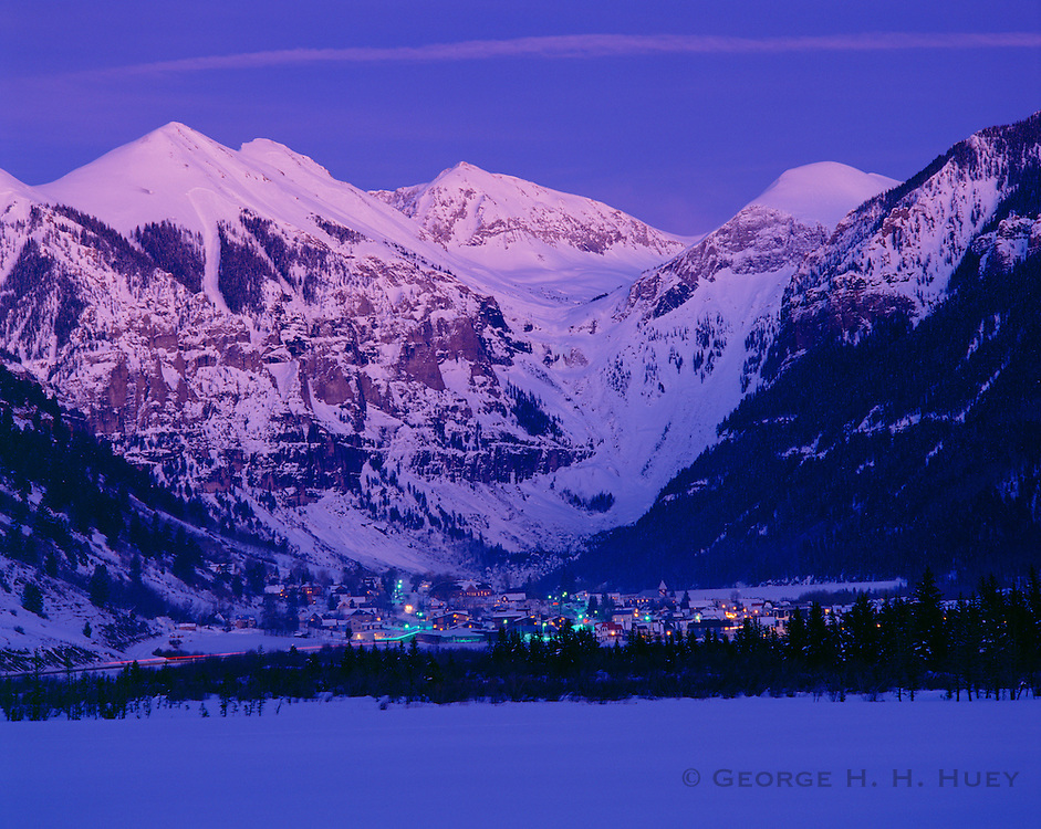 0481-1003B ~ Copyright: George H. H. Huey ~ The town of Telluride at dusk, winter, with the San Juan Mountains rising behind. San Miguel County. Telluride, Colorado.
