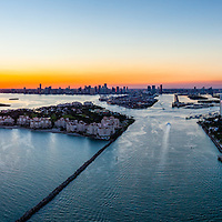 Aerial panorama view of Miami Beach Southpoint waterfront and Government Cut Port of Miami inlet at sunset.