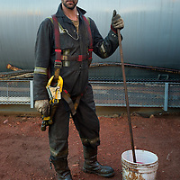Brian Coffey, a floor hand, stops for a moment to pose for a photo while cleaning the tops of a storage tank at the Raven Oil Drilling rig grounds near Watford City N.D., Oct 1, 2013.  In 2008 the North Dakota oil boom started its ongoing period of extraction of oil from the Bakken formation. Shale gas reserves has given the United States more independence over other nations such as Venezuela and countries in the Middle East.  Photo Ken Cedeno