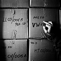 Bodies are stored in white body bags and cardboard boxes in refrigerated storage containers, awaiting identification or reburial.