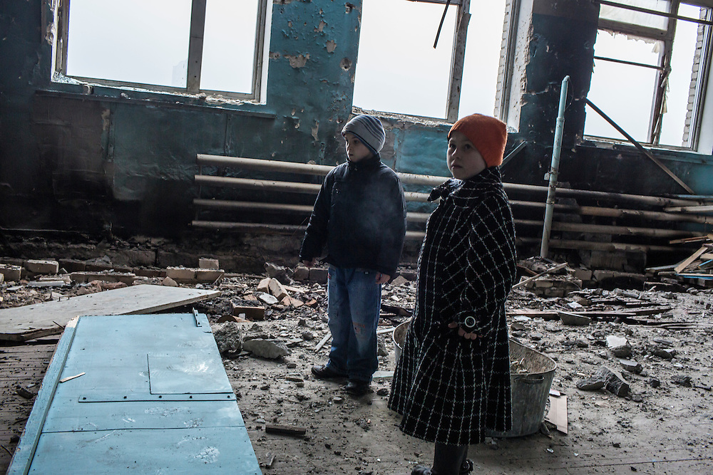 Students stand amid rubble in their school's gymnasium, which was hit by a shell earlier in the year, on Friday, December 11, 2015 in Troitske, Ukraine.