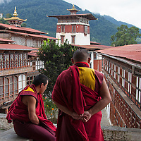 Asia, Bhutan, Trongsa. Monks at Trongsa Dzong overlooking courtyard.