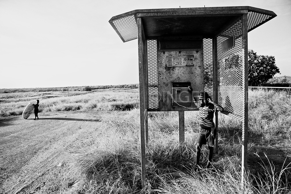 While the rest of the world takes for granted wifi connections, hot spots, internet cafes etc some places remain locked in the past in regards to technology.<br /> Romania playing in a phone booth at Morgan Camp and yes the phone is working. <br />Broome, Western Australia &copy;Ingetje Tadros