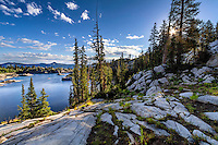 Sun shines through the trees overlooking Lake Mary in Utah's landscape photography backcountry.