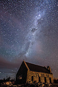 The Milky Way shines through patchy clouds, above the Church of the Good Shepherd, at Tekapo, New Zealand.