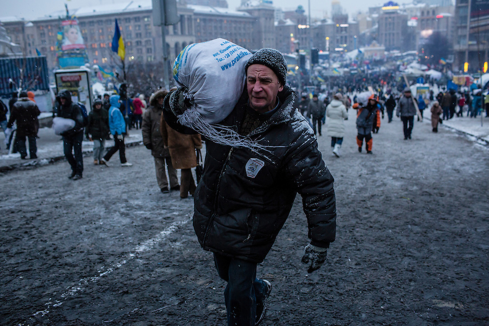 KIEV, UKRAINE - DECEMBER 11: An anti-government protester carries a bag of snow to be used to reinforce a barricade blocking street access to Independence Square, known as the Euromaidan, on December 11, 2013 in Kiev, Ukraine. Thousands of people have been protesting against the government since a decision by Ukrainian president Viktor Yanukovych to suspend a trade and partnership agreement with the European Union in favor of incentives from Russia. (Photo by Brendan Hoffman/Getty Images) *** Local Caption ***