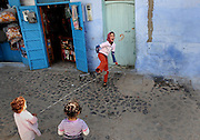 """A girl laughs while she plays a skipping game with some friends in Chefchaouen, Morocco, whose """"medina"""" (old city) is famous for its striking blue walls."""