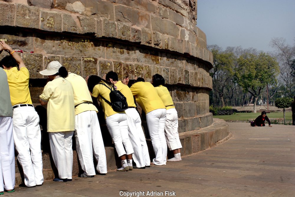 Buddhist pilgrims at the holy Sarnath in Varanasi. This is the spot where Buddha gave his first sermon. Pilgrims come from all over the world to pay their respect, with some circumnavigating the stone structure many times in a prostrate position.