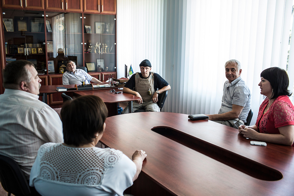 DOBROPILLYA, UKRAINE - MAY 21:  Members of the Donbass Battalion, a pro-Ukraine militia, meet with Mayor Victor Derivasko (2nd L) to ensure the integrity of the upcoming presidential election on May 21, 2014 in Dobropillya, Ukraine. Days before presidential elections are scheduled, questions remain whether the eastern regions of Donetsk and Luhansk are stable enough to administer the vote. (Photo by Brendan Hoffman/Getty Images) *** Local Caption *** Victor Derivasko