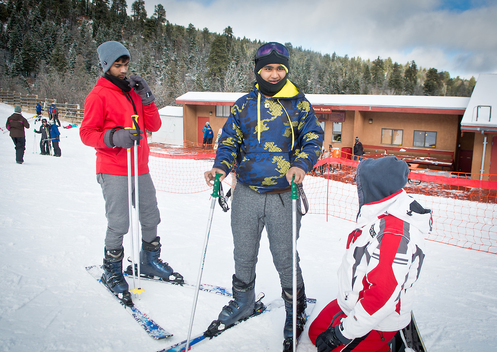 mkb122316b/metro/Marla Brose122316<br /> Vivek Patel, center, takes a look at the ski hill before heading out with his cousin Sachin Patel, left, and his uncle Anil Patel, right, who was helping Vivek with his bindings, Friday, Dec. 23, 2016, on the first day of the season at Sandia Peak Ski Area. Anil Patel, who lives in Dallas, surprised his nephews by stopping in Albuquerque and taking them skiing. Only the beginner hill is open until more snow falls. (Marla Brose/Albuquerque Journal)